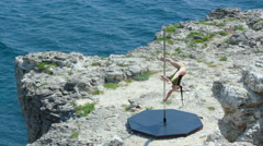 Slow motion of strong girl performing pole dance tricks on rocky cliff by sea Stock Footage
