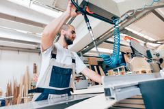 Low angle view of young man in workshop using carpentry equipment Stock Photos