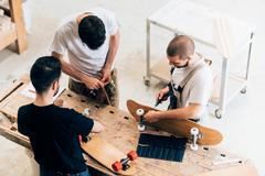 High angle view of young men standing around workbench attaching wheels to - stock photo