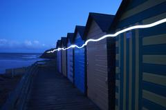 Row of colourful beachhuts at dusk, with light trail, Bude, Cornwall, UK Stock Photos