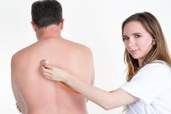 Female doctor Examine Patient's Back With Stethoscope Stock Photos