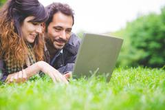 Head and shoulders of young couple lying on front on grass using laptop computer - stock photo