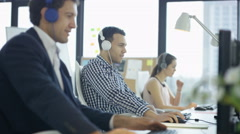 4K Happy workers in office working & listening to music through headphones Stock Footage