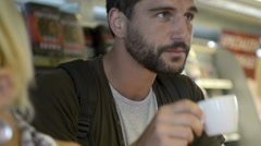 Young beautiful man have breakfast with cappuccino at service station Stock Footage