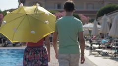 Young man and girl go hand in hand, along the pool Stock Footage