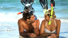 Young couple wearing diving mask lying on beach Stock Footage