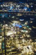 Aerial view of oil refinery and storage tanks illuminated at night, Los Angeles, - stock photo