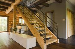 Wood stairway with wrought iron railings in modern Eastern white pine log cabin Stock Photos