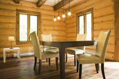 Dining table and chairs with modern lighting in Eastern white pine log cabin Stock Photos