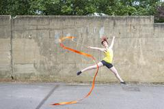 Young woman practising ribbon dance on court Stock Photos