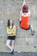 Young women climbing over wall with rope Stock Photos
