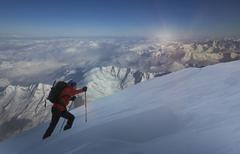Climber moving up through deep snow, Swiss Alps, Canton Wallis, Switzerland - stock photo
