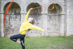 Young woman practising ribbon dance, walled arches in background Stock Photos