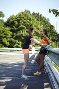 Two young female runners tying trainer laces in parking lot - stock photo