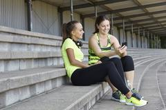 Two young female runners chatting in stadium seating - stock photo