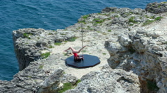 Graceful poledancer doing pole dancing fitness exercise on edge of rocky cliff Stock Footage