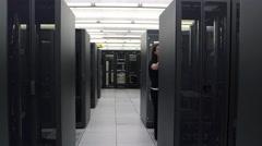 Walking view of three people working in network server room Stock Footage