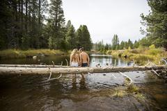 Rear view of romantic young couple sitting on fallen tree in river, Lake Tahoe, - stock photo