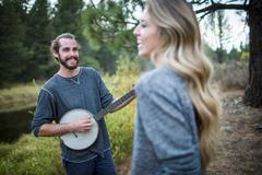 Young couple playing banjo at riverside, Lake Tahoe, Nevada, USA Kuvituskuvat