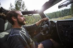 Young man driving jeep on road trip, Lake Tahoe, Nevada, USA - stock photo