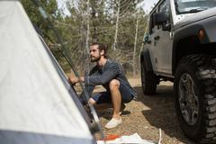 Young man erecting tent in forest, Lake Tahoe, Nevada, USA - stock photo