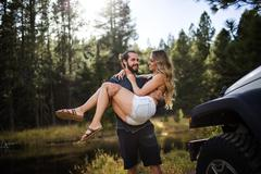 Romantic young man carrying girlfriend on riverside, Lake Tahoe, Nevada, USA Stock Photos