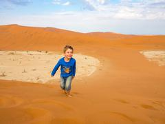 Little boy playing in the sand dunes, in the sandbox, Sossusvlei in Namibia Stock Photos