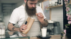 Barista pours beans into a container Stock Footage