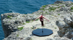 Slow motion of poledancer performing pole trick on the edge of rocky cliff Stock Footage