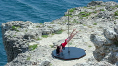 Pole dancing fitness exercise on the edge of rocky cliff by sea slow motion Stock Footage
