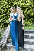 Teenage girls wearing prom dresses holding champagne flute looking at camera Stock Photos