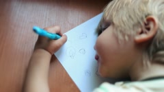Cute baby boy age of two, kid toddler child learns to write, draw  Stock Footage