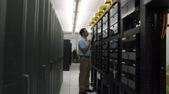 Dolly shot of man looking at network server Stock Footage