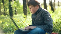 Teen boy child with a PC laptop, communicate via Internet by notebook outdoor - stock footage