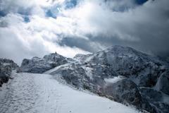 Hiker on snowy mountaintop - stock photo