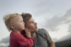 Female toddler and father looking up and watching - stock photo