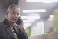 Senior businesswoman chatting on smartphone in hotel lobby - stock photo