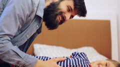 Little smiling boy lying on bed playing with his bearded father Stock Footage