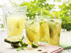Glasses of home made golden rum punch with lime, pineapple, mint and ice - stock photo