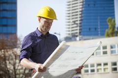 Building contractor wearing hard hat looking at blueprint Stock Photos