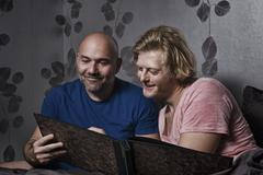 Male couple sitting up in bed looking at photo album - stock photo