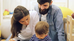 Family with baby boy sitting on floor at home and playing together - stock footage