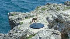 Professional poledancer performs pole tricks and spins on rocky cliff by sea Stock Footage