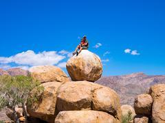 Father and son sitting on rocks, climbing the Brandberg - stock photo