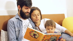 Happy family with cute boy reading book before going to bed Stock Footage