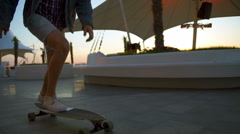 Close up male legs riding longboard on seafront at sunrise slow motion Stock Footage