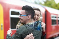 Heterosexual couple hugging at railway station, smiling Stock Photos