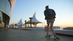 Handsome man skateboarding at seafront at sunrise slow motion Stock Footage