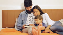 Happy family, mother ,father and their baby read a book at home Stock Footage