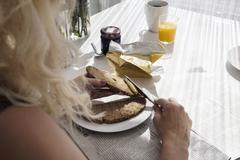 Over shoulder view of mature woman spreading butter onto bread - stock photo